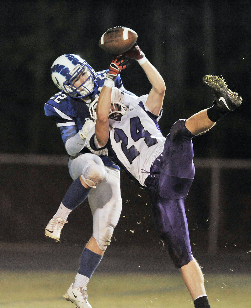 Noah Kreider of Marshwood, foreground, breaks up a pass intended for Larson Coppinger of Kennebunk in the second quarter Friday night. Kennebunk won 21-14 in a game between undefeated Western Class B opponents.
