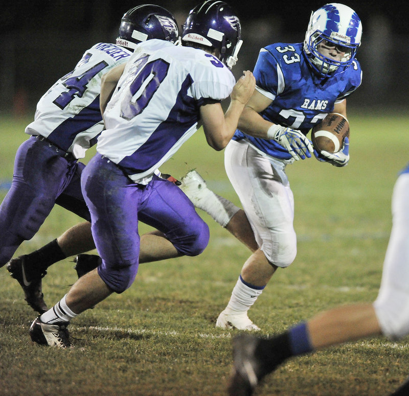 Nicco DeLorenzo of Kennebunk looks for a way to turn the corner against Noah Kreider, left, and Zach Doyon of Marshwood.
