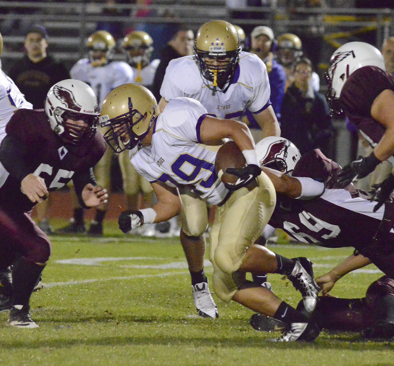 Cody O'Brien of Cheverus finds room to gain yards Friday night as Tyrell Gullatt of Windham attempts to make the tackle. Cheverus, ahead 28-14 at halftime, pulled away to a 57-22 victory at Windham.