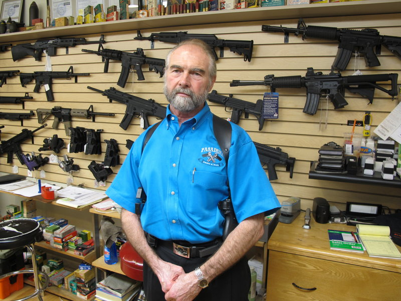 Frank Loane with assault rifles at his store in Pasadena, Md., on Thursday.