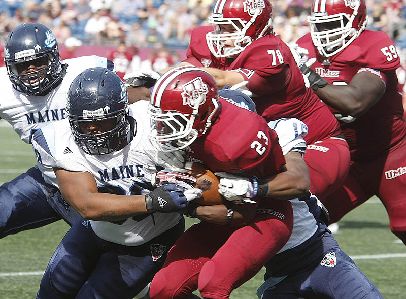 Darius Green, left, and Jamal Clay bring down UMass running back Stacey Bedell, part of a UMaine defensive effort that limited the Minutemen to 265 yards.