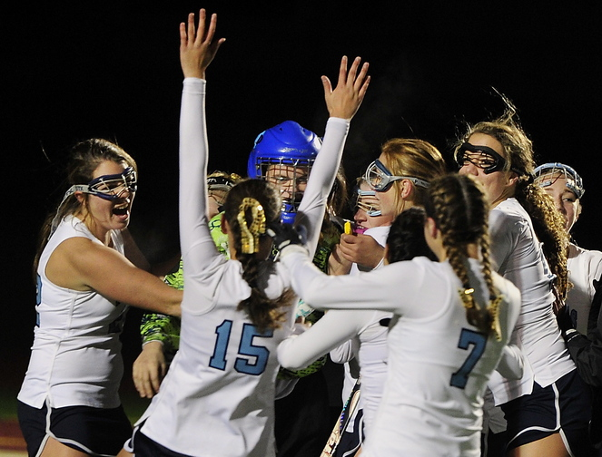 York players hug goalie Olivia Golini as they celebrate their 6-0 win over Spruce Mountain in the Western Class B field hockey championship game Tuesday at Thornton Academy.
