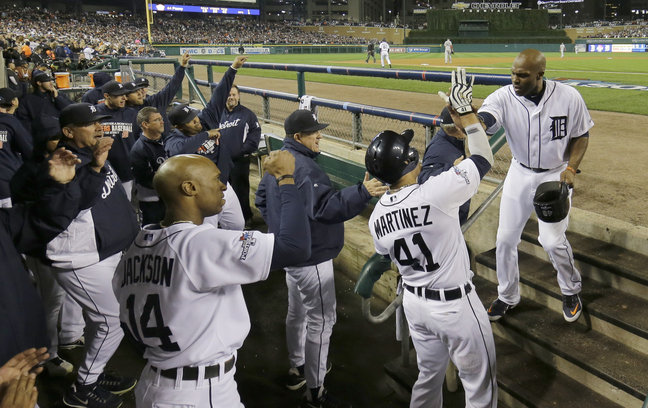 Torii Hunter of the Detroit Tigers is greeted by Victor Martinez after scoring on a single by Miguel Cabrera in the second inning of Game 4.