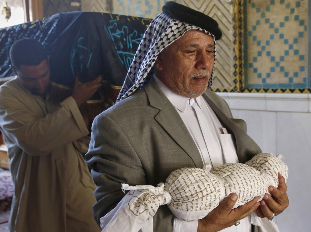 Mahmoud Abdel-Rahman carries the body of his 11-month-old grandson, who was killed along with his mother when their house collapsed in a car bombing.