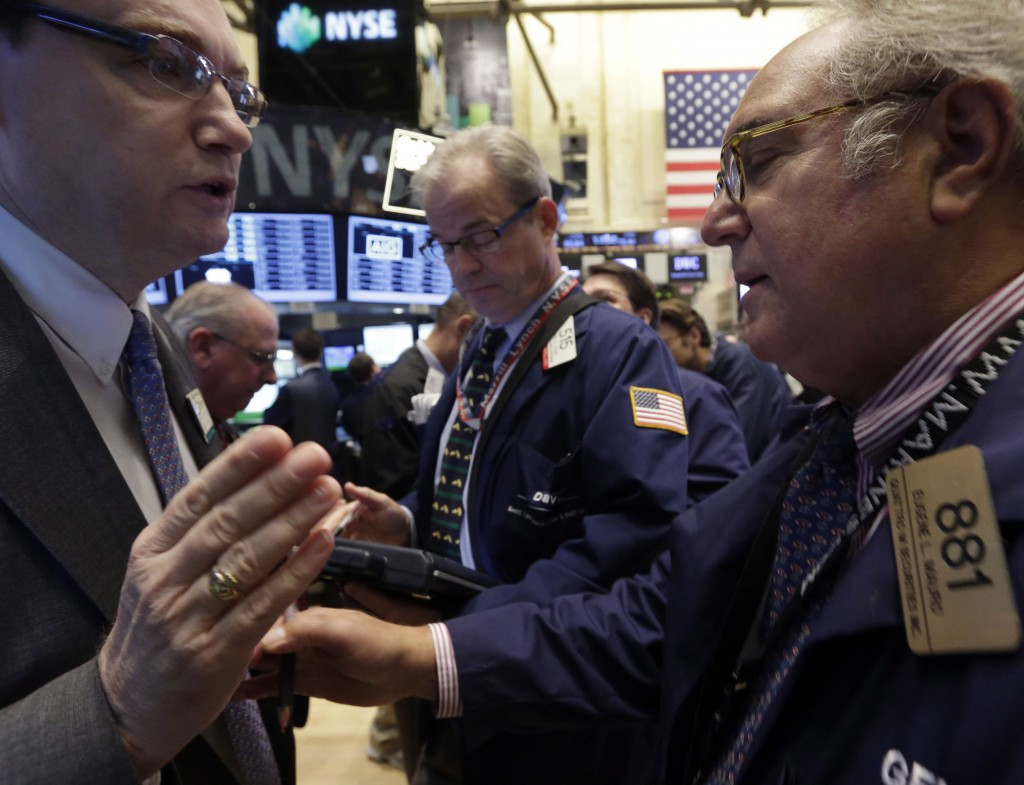 Specialist Patrick King, left, talks with trader Eugene Mauro on the floor of the New York Stock Exchange on a day when the Dow Jones industrial average soared 323 points because of hopeful signs that a budget impasse in Washington may break soon.