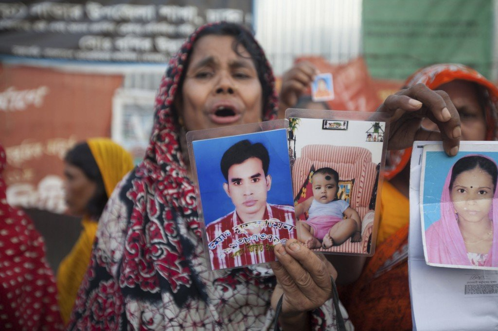 A woman displays photographs of loved ones on Thursday, the six-month anniversary of the Rana Plaza factory collapse.