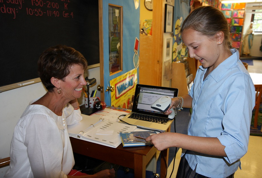 Jenny Hall, left, head librarian and volunteer at Holy Cross Catholic School in South Portland, helps student Emma Langevin check the barcode on a book as part of the school library's recent upgrade to make more than 4,000 books available via Web-based software.