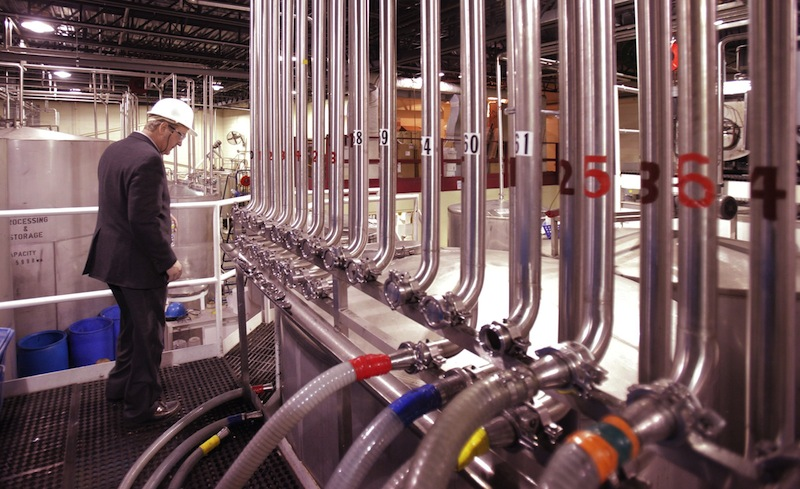 John Suczynski walks past a row of stainless steel pipes that transport alcohol to the bottling lines at White Rock Distilleries in Lewiston in 2011.