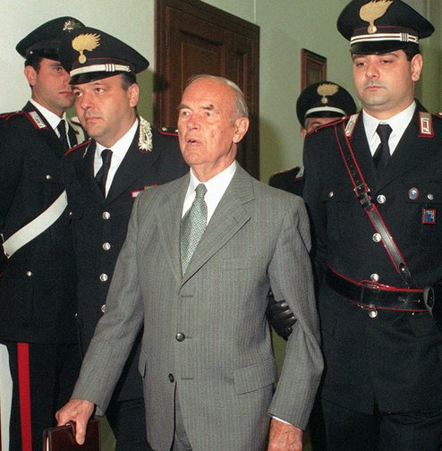Former German SS officer Erich Priebke enters a military court in Rome in 1996. He eventually was sentenced to life in prison for his role in World War II atrocities. Because of his age, he served his term under house arrest. He died Friday.