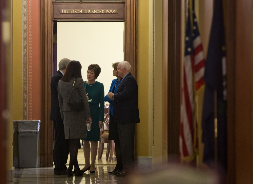 Sen. Susan Collins, R-Maine, center, talks with, from left, Sen. Rob Portman, R-Ohio, Sen.. Kelly Ayotte, R-N.H., Sen. Lisa Murkowski, R- Alaska, and Sen. John McCain, R- Ariz., on Capitol Hill in Washington, on Friday. Republicans are offering to pass legislation to avert a default and end the 11-day partial government shutdown as part of a framework that would include cuts in benefit programs, officials said Friday.