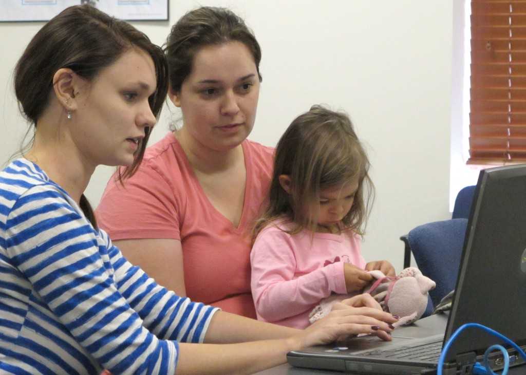 Debora Costa right, tries to sign up for insurance coverage for her two children, including 2-year-old Victoria, Wednesday, Oct. 2, 2013, with help from Champaign Urbana Public Health District employee Alice Cronenberg in Champaign, Ill. Costa, who recently moved to Illinois from Brazil with her graduate-student husband and children, found after about 10 minutes that she didn't have all the information she would need to sign up.