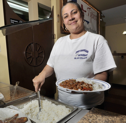 Server Mayda Perez serves up a plate of rice and beans at Tipico Dominicano Restaurant in Portland.