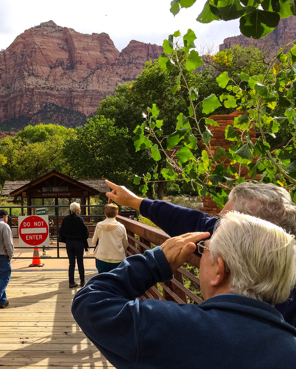Tourists point out landmarks visible from the gate to Zion National Park in Utah, which is closed because of the federal shutdown.