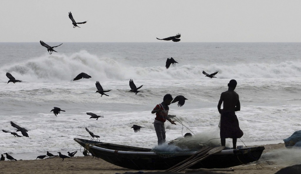 Indian fishermen sort their nets after returning with their catch off the Bay of Bengal. The country is preparing for a cyclone of deadly proportions.