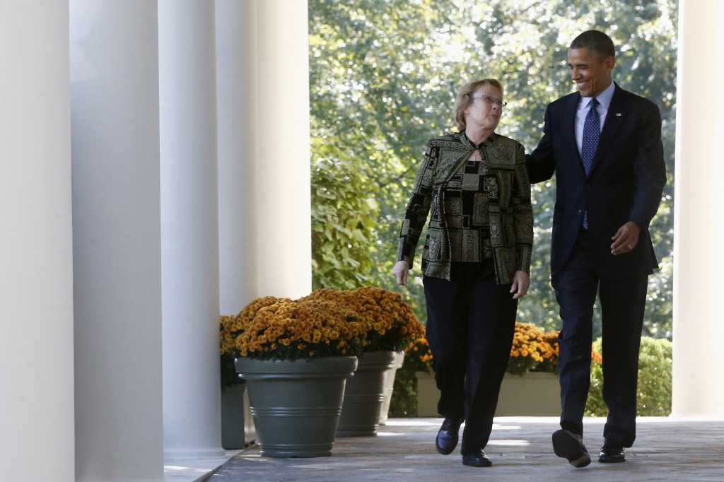 In this Oct. 21 file photo, President Barack Obama walks from the Oval Office to the Rose Garden of the White House in Washington with Janice Baker, who runs a small business in Selbyville, Del., and was the first woman to enroll in the Delaware health care exchange, for an event on the initial rollout of the health care overhaul. The Obama administration says it's granting a six-week extension until March 31 for Americans to sign up for coverage next year and avoid new tax penalties under the president's health care overhaul law.