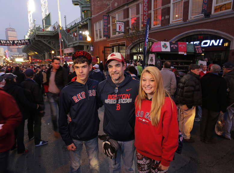 "Gabe Souza/Staff Photographer Lance Richmond of Pittsfield stands with his 14-year-old twins, Carter and Emily, on Landsdowne Street outside Fenway Park before the start of Game 6. ""We're all in,"" Richmond said. ""The Red Sox are winning it tonight. We don't have tickets for Game 7."""