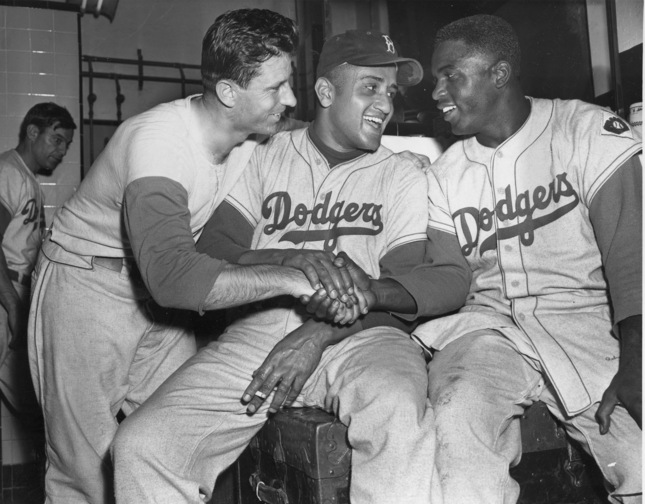 "Brooklyn Dodgers baseball player Andy Pafko, left, Don Newcomb, center, and Jackie Robinson shake hands in their dressing room after the Dodgers beat the Philadelphia Phillies 5-0, in New York. That flowing blue ""Dodgers"" script across the front of the jersey that followed them from Brooklyn."