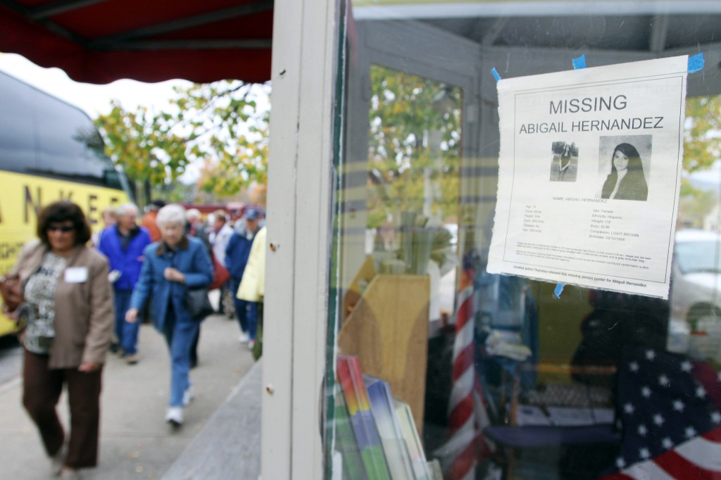 In this photo taken Wednesday Oct. 16, 2013, tourists walk by an information booth with a poster of missing teenager Abigail Hernandez in North Conway, N.H. Hernandez disappeared Wednesday Oct. 9 when she was last seen leaving school and walking towards home.