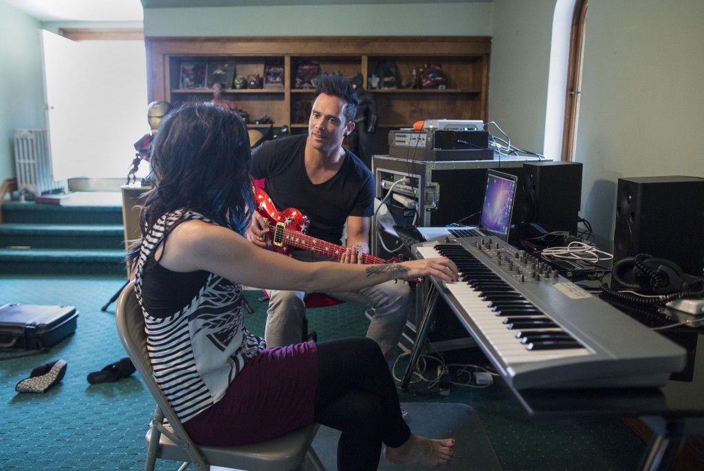 "In this July 22, 2013 photograph, married musicians Korey Cooper, left, and John Cooper of the Christian rock band Skillet play music inside of their home in Kenosha, Wis. Skillet released its eighth album ""Rise,"" this June _ coming off its best-selling album ""Awake,"" which went platinum after three years. (AP Photo/Scott Eisen)"