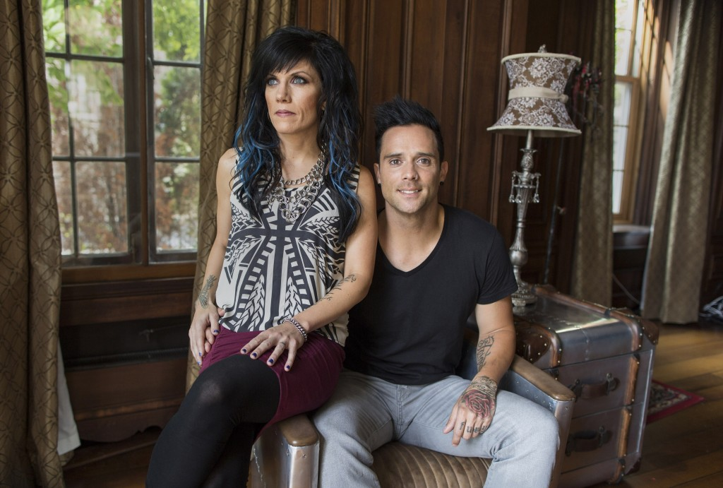 "In this July 22, 2013 photograph, married musicians Korey Cooper, left, and John Cooper of the Christian rock band Skillet pose for a portrait inside of their home in Kenosha, Wis. Skillet released its eighth album ""Rise,"" this June _ coming off its best-selling album ""Awake,"" which went platinum after three years. (AP Photo/Scott Eisen)"