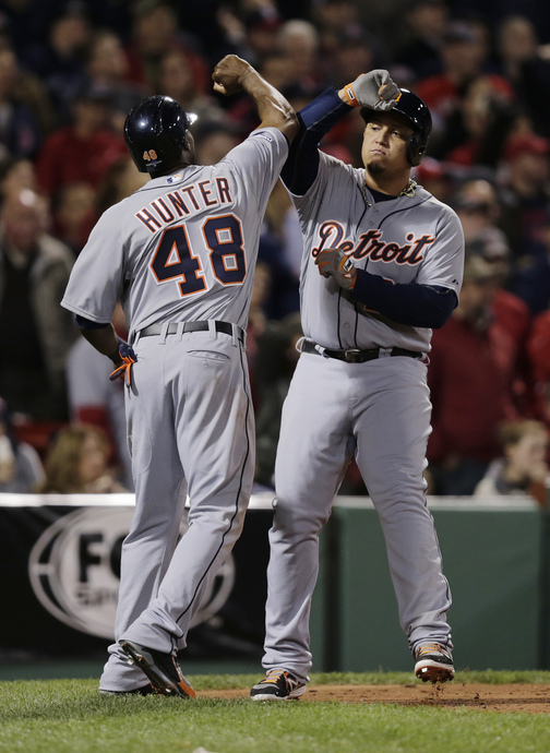 Detroit Tigers' Torii Hunter (48) and Miguel Cabrera celebrate after they both scored against the Boston Red Sox inning during Game 6 of the American League baseball championship series on Saturday, Oct. 19, 2013, in Boston.. (AP Photo/Charles Krupa)