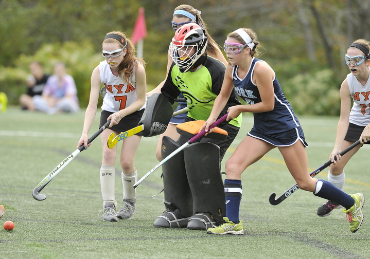 York's Taylor Simpson (right), moves in for a rebound after a defensive effort by NYA goalie Elizabeth Coughlin and teammate Charlotte Eisenberg (left) during York's 4-0 win on Tuesday. York is now 14-0: NYA falls to 11-2-1.