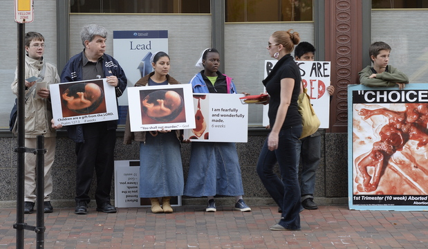 Shawn Patrick Ouellette/Staff Photographer A pedestrian walks past anti-abortion protesters on Congress Street in Portland near the Planned Parenthood clinic Friday.