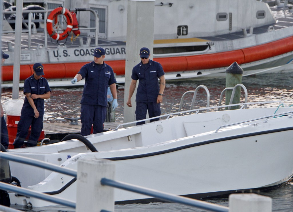 Coast Guard personnel inspect a vessel with a missing center console that capsized early Wednesday about seven miles east of Miami, killing four of the 15 people on board.
