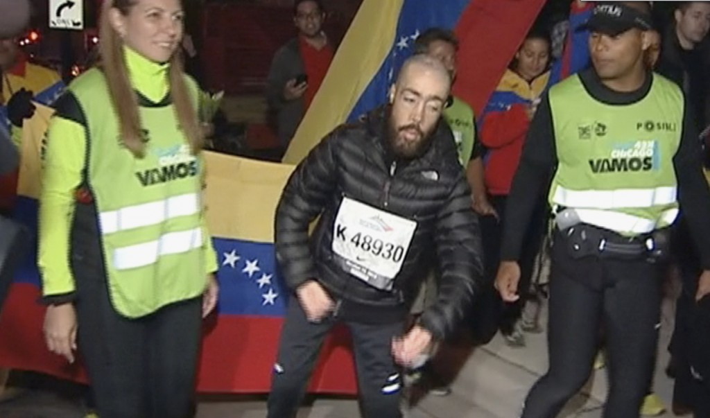 "Maickel Melamed, 38, center, of Venezuela, who has muscular dystrophy, nears the finish line Monday at the Chicago Marathon – nearly 17 hours after he started. About 100 people cheered him on. ""When you give it all you feel peace inside,"" he said."