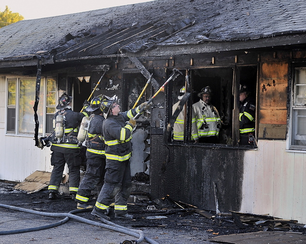 Gordon Chibroski, Staff Photographer Scarborough firefighters search for hot spots Tuesday at the Itsa Good Motel as the chief and deputy investigate inside the room after the fire was put out.