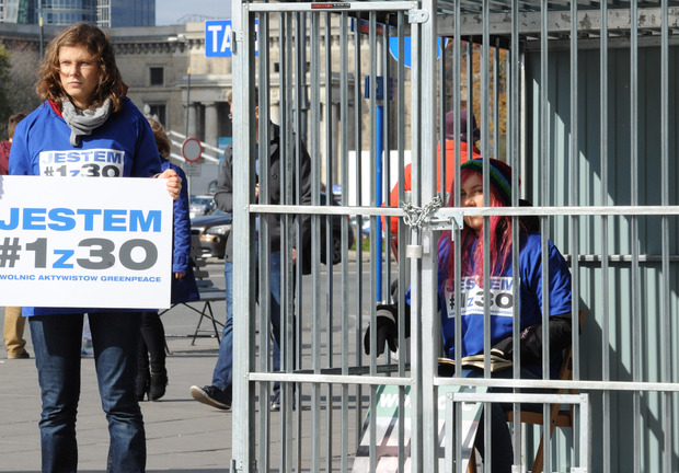 "One Greenpeace activist sits in a cage in Warsaw, Poland, while another one holds a placard reading ""I am 1 of the 30"" in a protest against Russia's jailing of Greenpeace activists."
