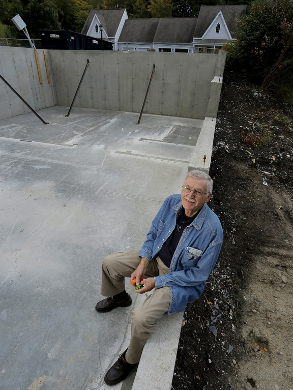 Amory Houghton, 83, sits on the foundation of his house on Gables Drive in Yarmouth last week. His condo unit is being rebuilt after a propane explosion in June made his unit uninhabitable.