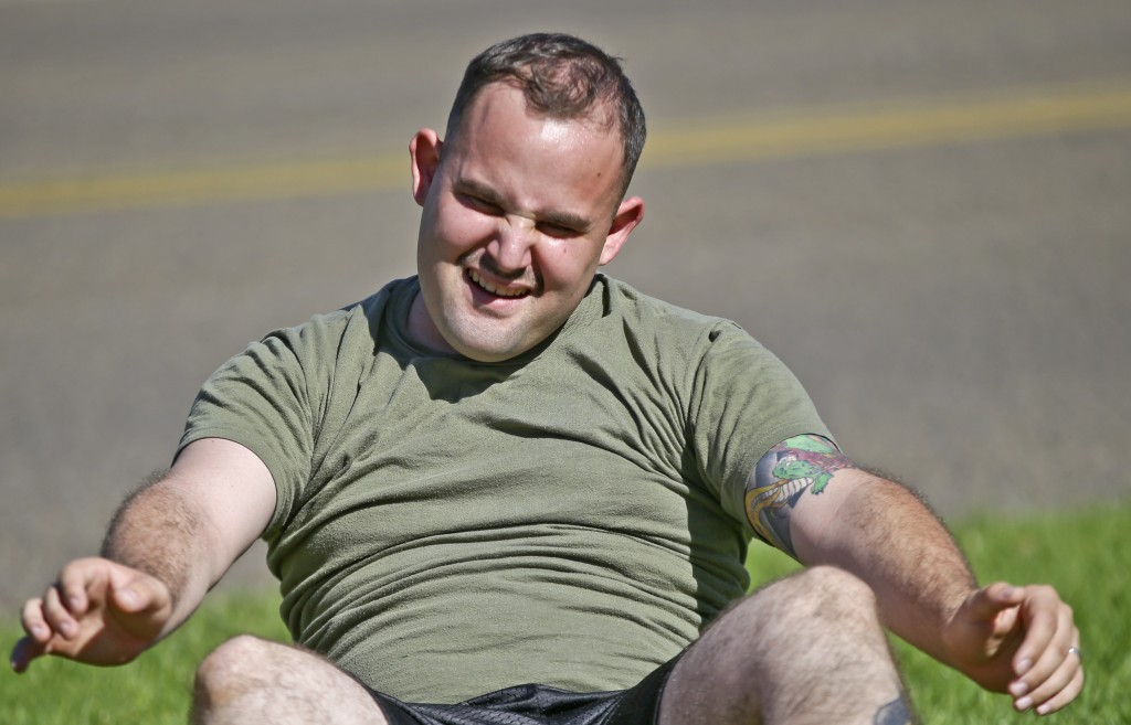 "A service member who failed the so-called ""tape test"" struggles doing sit-ups during a workout where he hopes to improve his conditioning and avoid being dismissed from the military, at the Marine Corps Recruit Depot in San Diego. Marines have nicknamed the program for those who fail the test ""pork chop platoon"" or ""doughnut brigade."""