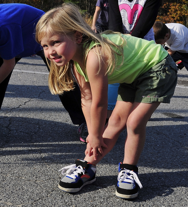 Sebago Elementary School kindergartener Audrey Dubay warms up with other kids before running on Monday.
