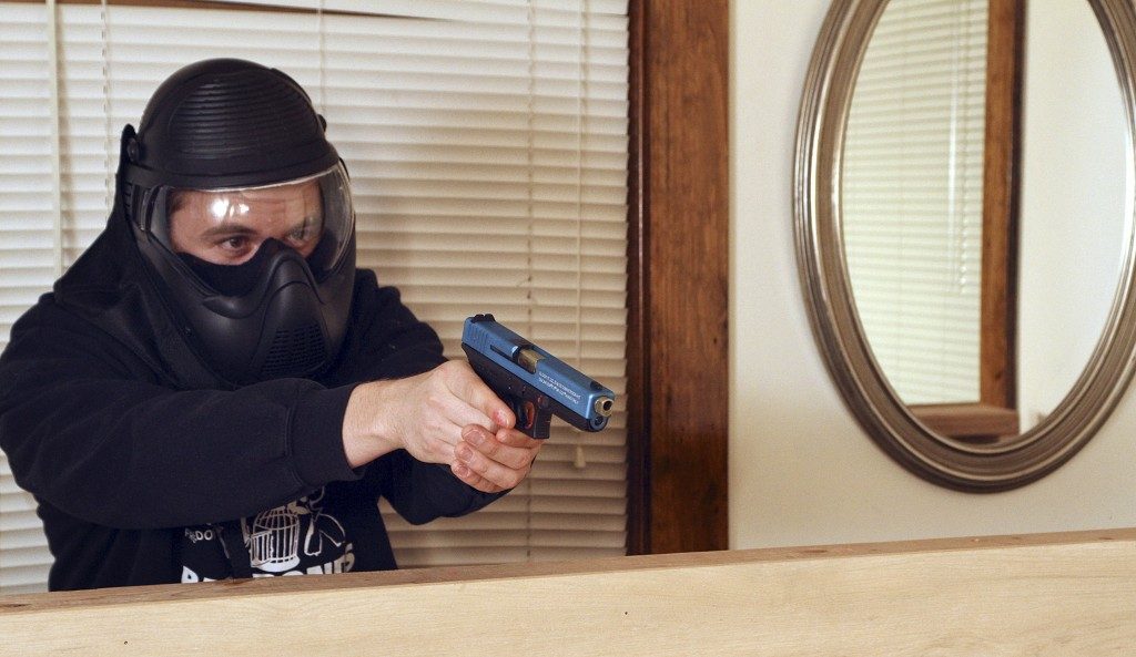 Firearms safety instructor Andrew Hyduchak wears protective gear as he aims a Glock pistol loaded with nonlethal Simunition training ammunition while acting in the role of a home invader.