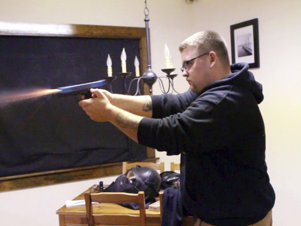 Joe Arnson fires a Glock pistol loaded with nonlethal Simunition training ammunition as part of a home invasion training course at Prepare to Act firearm safety training company in Watertown, Conn.