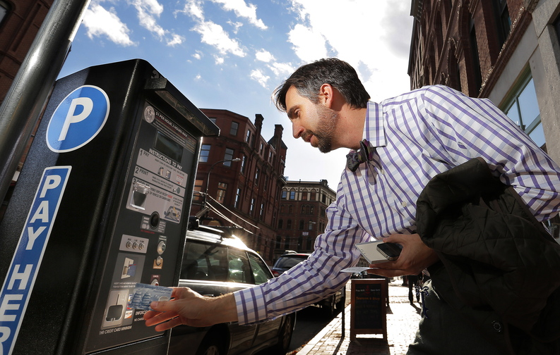 Jim Krebs of Portsmouth, N.H., who works in Portland at the University of New England, uses his credit card to pay for parking at one of the city's new parking kiosks on Middle Street Friday afternoon. Krebs said he's used to the kiosks because they're everywhere in Portsmouth, and are much easier when he's not carrying cash.