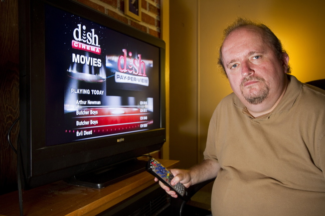 Tim Ryan of Lisbon sits in front of his television with Dish Network service last month. Ryan canceled his Time Warner TV service in favor of the DISH network after eight years as a Time Warner customer. He said price increases and rigid customer service representatives – who shut his service off after he missed his bill deadline by a day – convinced him to drop the cable provider.