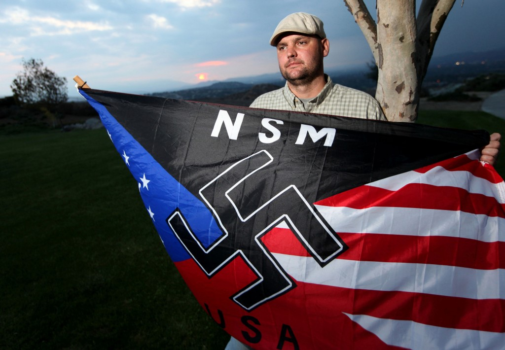 In this Oct. 22, 2010, photo, Jeff Hall, who was killed by his son, holds a neo-Nazi flag while standing in a park near his home in Riverside, Calif.