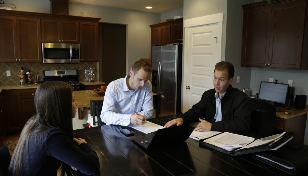 Insurance broker Jeff Lindstrom, right, meets with Brandi and Darren Litchfield to discuss health insurance plan options, at their home in the Seattle suburb of Bothell, Wash. Darren works for a startup company that doesn't yet offer an employee insurance plan, so they invited Lindstrom to outline the options of different healthcare plans that he offers as a broker.