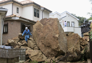 A firefighter walks over debris in Kamakura, Japan, after a powerful typhoon hit the metropolitan area Wednesday.