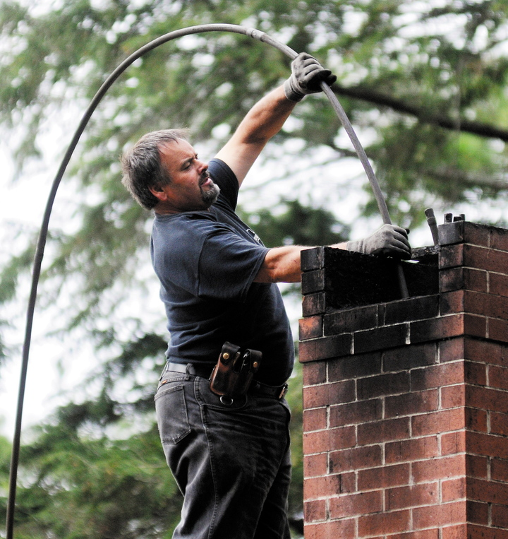 Dave Pelletier of Downeast Chimney sweeps a flue on a home in Litchfield this week.