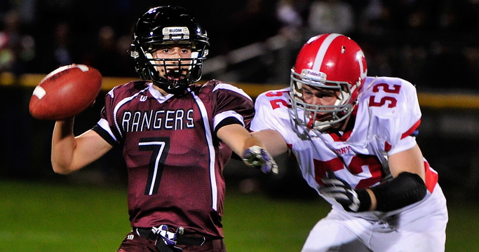 Greely quarterback Matt Pisini looks for a receiver as Alex Neill of Cony closes in during their Class B football game Friday night in Cumberland. Pisini threw two touchdown passes and rushed for two scores in Greely's 35-21 upset victory.