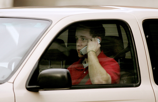 A teen driver talks on a cell phone in Salt Lake City. According to a new study from an insurance research group, the expense of driving trumps other factors in leading to fewer people getting driver's licenses during their teenage years.