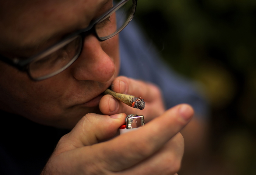 Crash Barry, a writer from Oxford County who grows marijuana for medicinal use, lights a marijuana cigarette in Portland last week.