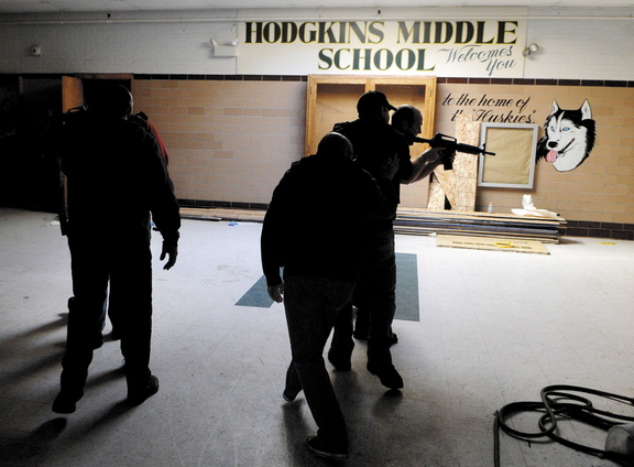 Augusta emergency responders stay low as they follow Augusta police officers into a simulated school shooting incident during a training exercise Thursday at the former Hodgkins Middle School in Augusta.