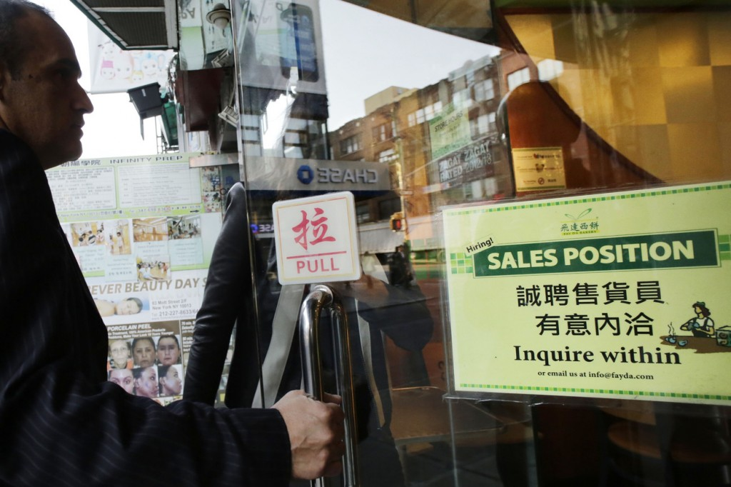 "A customer enters a Chinese bakery that has a sign posted in the door, ""Hiring! Sales Position Inquire within,"" Tuesday in New York. The U.S. economy added just 148,000 jobs in September, suggesting that employers held back on hiring before a 16-day partial government shutdown began Oct. 1. Still, hiring last month was enough to lower the unemployment rate."