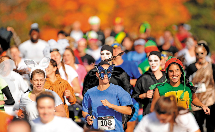 Nearly 200 costume-wearing runners make their way down Mayflower Hill Road at Colby College in the Freaky 5K Fun Run organized by Hardy Girls Healthy Women on Saturday. The fun run was started to help draw girls away from scantily clad Halloween characters and toward scary and creative costume designs.