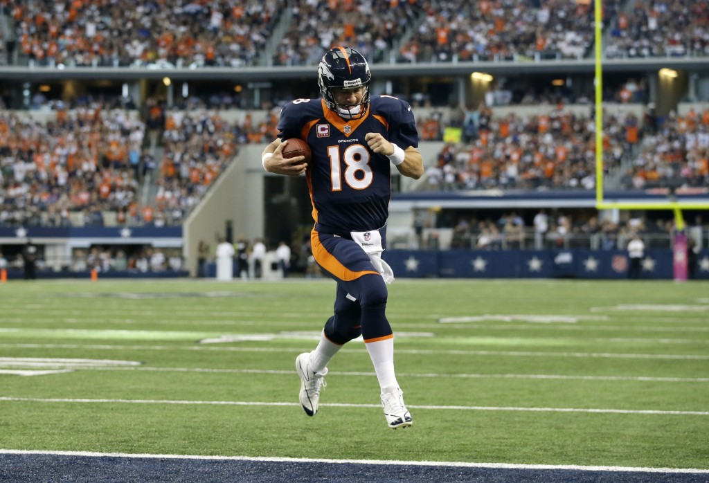 Denver Broncos quarterback Peyton Manning (18) sprints to the end zone untouched for a touchdown on a quarterback keep play in the first half of an NFL football game against the Dallas Cowboys, Sunday, Oct. 6,2013, in Arlington, Texas.