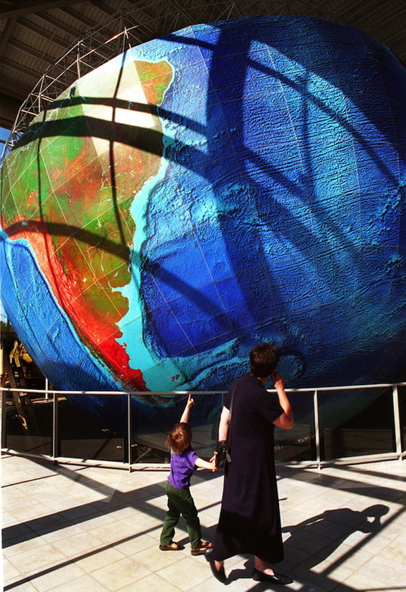 A boy and his mother enjoy the world-renowned 1:1,000,000-scale globe, which rotates on its axis and duplicates the earth's movement at DeLorme in Yarmouth. The map company confirmed Monday that it has laid off 10 of its 85 workers as part of its efforts to shift to digital products and away from traditional mapping services.